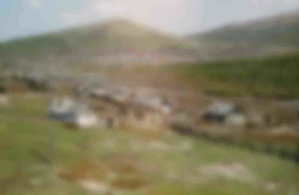 Wooden homes dot the landscape. Village seen from the train, location unknown.