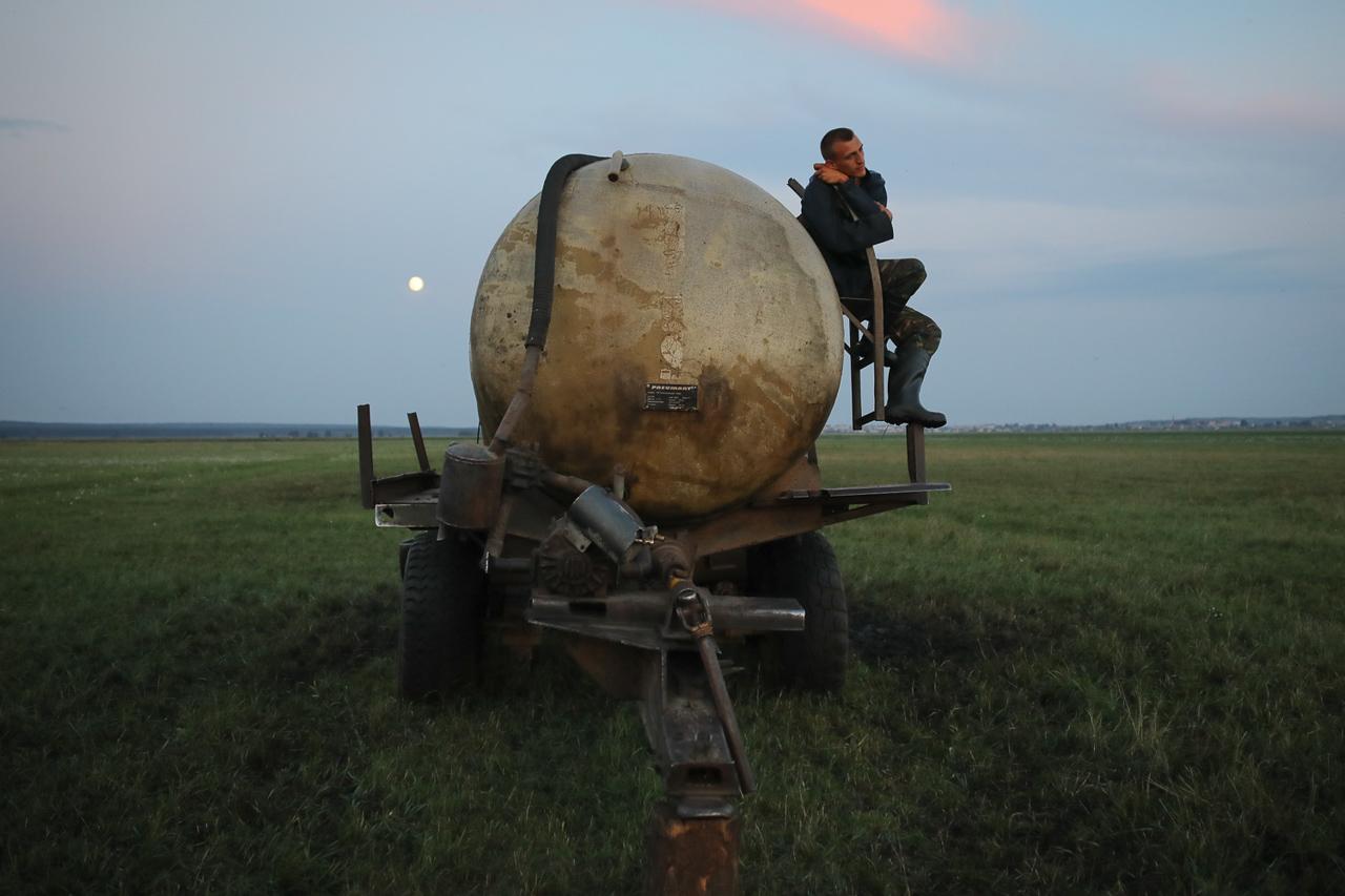 Пастух Дзьмітры Чашэйка сядзіць на бочцы з вадою на пашы