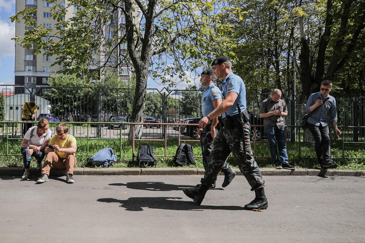 Супрацоўнікі АМАП праходзяць міма журналістаў БелаПАН, якіх не пускаюць у рэдакцыю падчас вобшуку